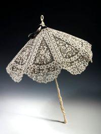 Parasol de 1870 feito de renda branca sobre renda preta com um elefante esculpido no cabo de marfim.