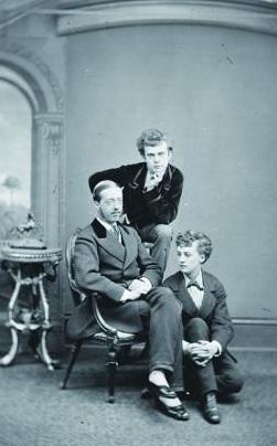 Com roupas masculinas, Lorde Arthur Pelham Clinton (sentado), Fanny (apoiada na cadeira) e Stella (no chão) posam para uma foto.
