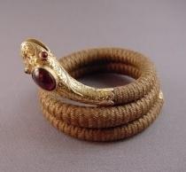 Bracelete feito de cabelo com cabeça de cobra feito de ouro e rubis.