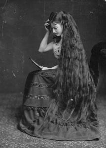 Em 1885, a Srta. Frampton arruma seus cabelos com a ajuda de um espelho.