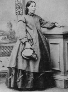 Margaret Gray, mulher grávida da Nova Zelândia, tenta disfarçar sua gravidez com um casaco largo na década de 1870.