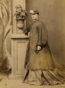 Mary Anne Downes, da Nova Zelândia, tenta disfarçar sua gravidez com um casaco largo na década de 1870.