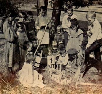 Funeral de um gato, década de 1880. É possível ver 15 crianças pequenas que realizam o funeral de seu gato em um cemitério.