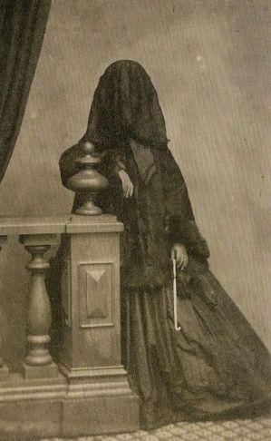 Fotografia de uma mulher em luto completo, por volta de 1860.