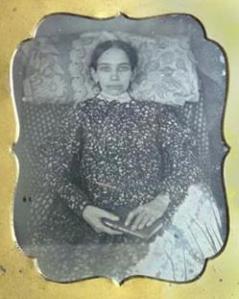 Fotografia post-mortem de uma jovem com um livro. Seus olhos foram pintados.